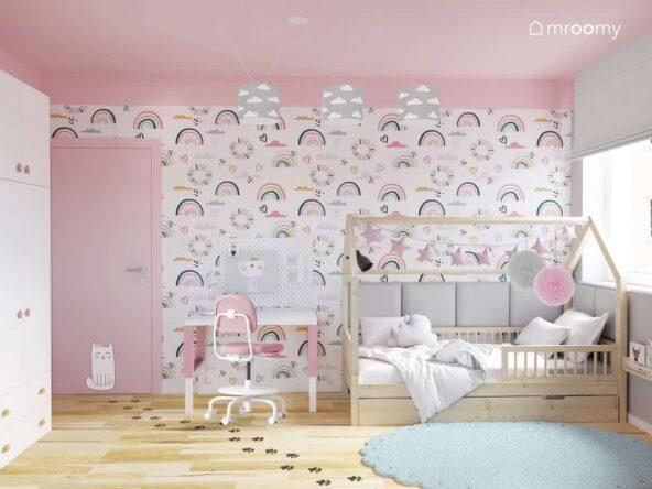 Różowo szary pokój dla dwóch dziewczynek z drewnianym łóżkiem domkiem biało różowym biurkiem z organizerem i ścianą pokrytą tapetą w tęcze
