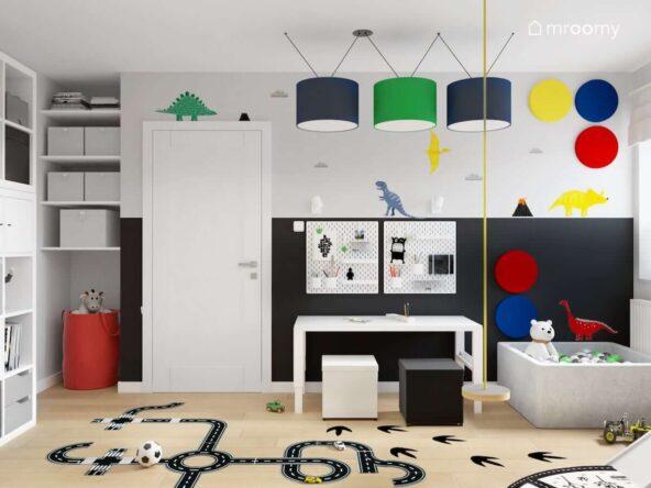 Biało-szaro-czarny pokój dla dwóch chłopców z białymi meblami basenem z kulkami ścianą z naklejkami w kształcie dinozaurów oraz lampą z granatowymi oraz zielonym abażurem