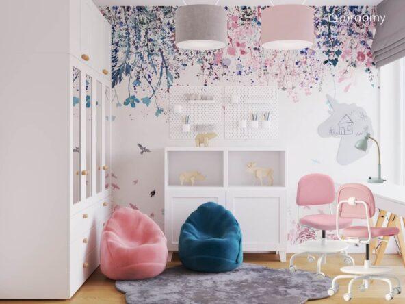 Jasny pokój dla dziewczynek a w nim szafa z lustrzanymi drontami różowy i niebieski worek do siedzenia białe komody organizery ścienne i kwiecista tapeta