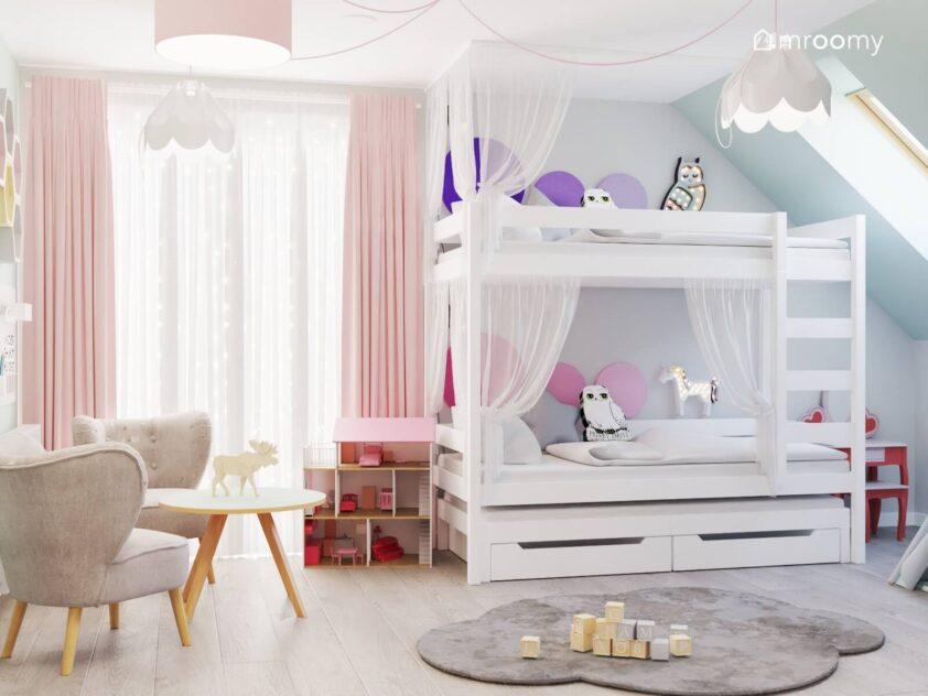 Kolorowy pokój dla dwóch dziewczynek ze stolikiem z dwoma fotelami oraz z białym łóżkiem piętrowym uzupełnionym firankami miękkimi panelami oraz dodatkami w kształcie sów