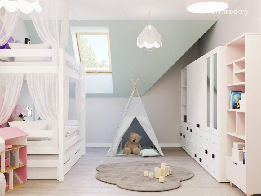 Poddaszowy pokój dla dwóch dziewczynek z łóżkiem piętrowym szafą z lustrzanymi frontami namiotem tipi dywanem w kształcie chmurki oraz białymi lampami sufitowymi