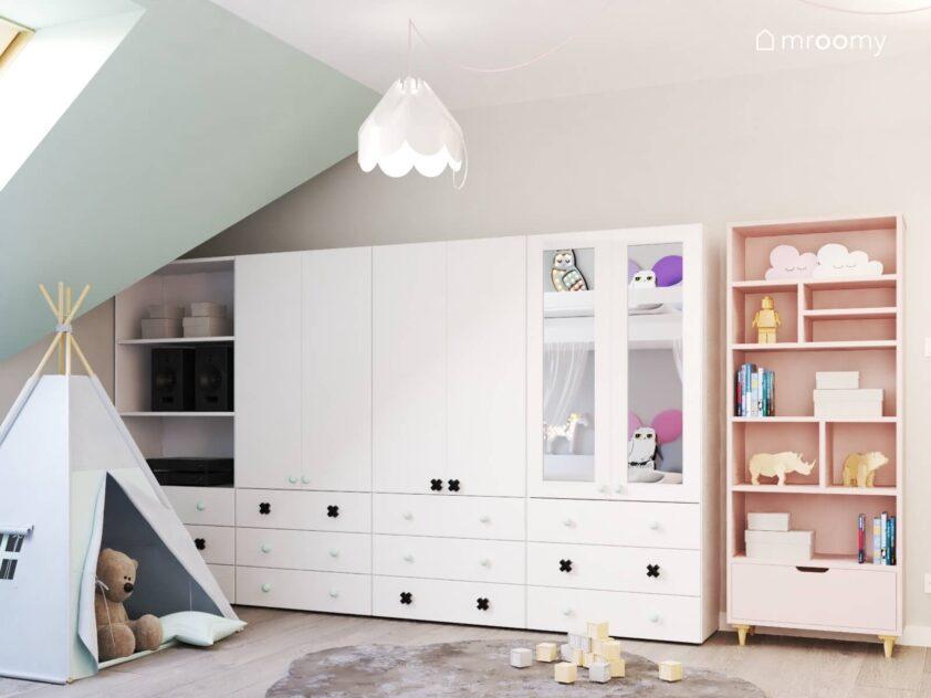 Duża biała szafa z lustrzanymi frontami i białymi i czarnymi gałkami oraz różowy regał w jasnym poddaszowym pokoju dwóch sióstr