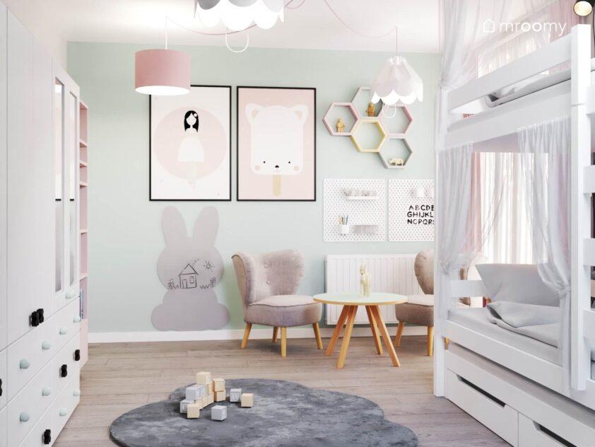Biało miętowy pokój dla dwóch dziewczynek a w nim łóżko piętrowe stolik na drewnianych nogach z fotelami organizery ścienne ozdobne plakaty i tablica kredowa w kształcie królika