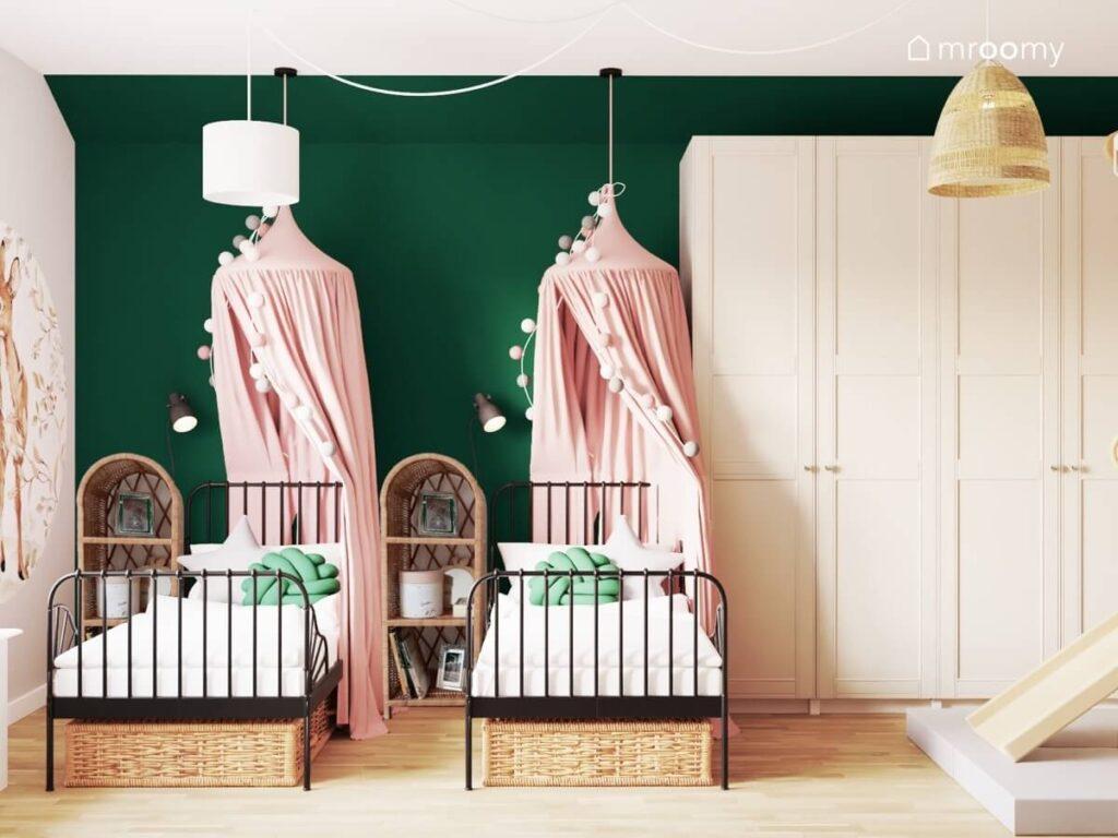 Biało zielony pokój dla dwóch dziewczynek a w nim jasnobeżowa szafa oraz czarne łóżka uzupełnione różowymi baldachimami i girlandami cotton balls i wiklinowymi szafkami