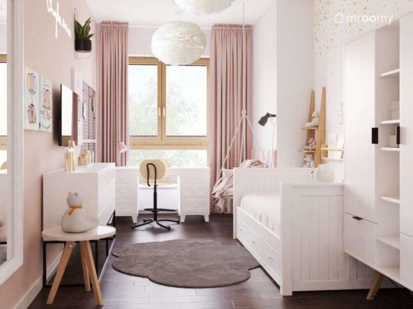 Delikatny biało różowy pokój dla dziewczynki z białym łóżkiem szafą na drewnianych nogach oraz biurkiem z dwoma komodami