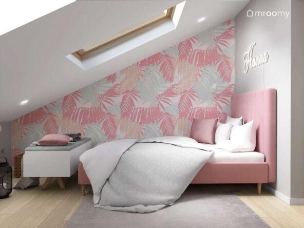 Strefa spania w poddaszowym pokoju dla nastolatki z różowym łóżkiem z wysokim zagłówkiem oraz ścianami ozdobionymi tapetą w liście i ledonem w kształcie imienia