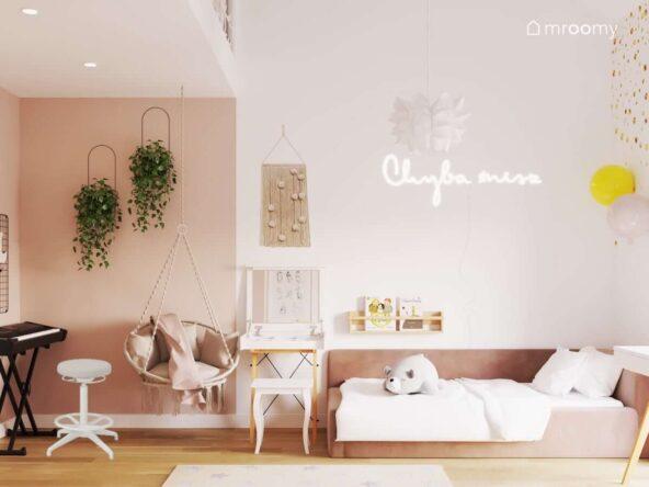Biało różowy pokój dla dziewczynki z różowym tapicerowanym łóżkiem toaletką fotelem wiszącym oraz ozdobnymi kwietnikami
