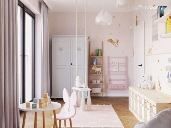 Różowy pokoik dla dziewczynki z wiszącą huśtawką z frędzlami różową biblioteczką drewnianym regałem w kształcie drabinki i miętową szafą