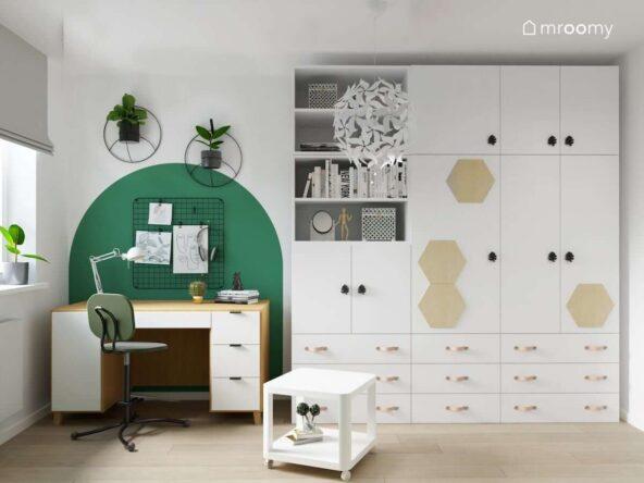 Duża biała szafa modułowa uzupełniona drewnianymi panelami i gałkami w kształcie liści a także biało drewniane biurko a nad nim organizer ścienny i ozdobne kwietniki w pokoju dla nastolatki