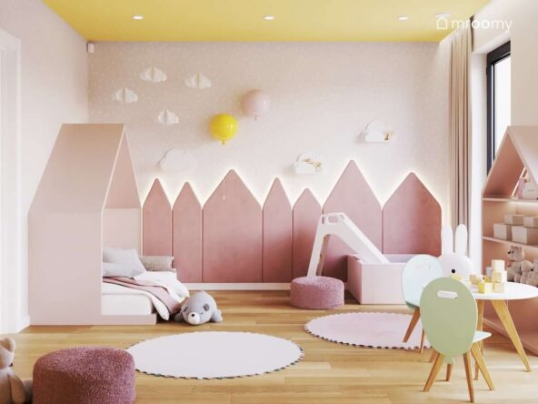 Różowy pokój dla małej dziewczynki z żółtym sufitem panelami ściennymi w kształcie trójkątnych domków oraz ozdobami w kształcie chmurek i kinkietami balonami