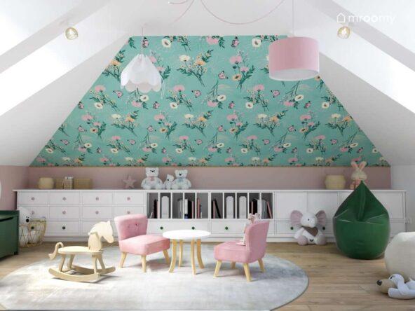 Skos pokryty kwiecistą tapetą a także niska zabudowa meblowa i okrągły stolik z różowymi welurowymi fotelikami w pokoju dla małej dziewczynki