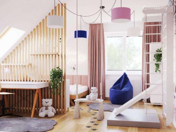Jasny pokój dla dziewczynki z białym biurkiem na drewnianych nogach huśtawką pokojową drabinką gimnastyczną ze zjeżdżalnią oraz lampą sufitową z kolorowymi abażurami