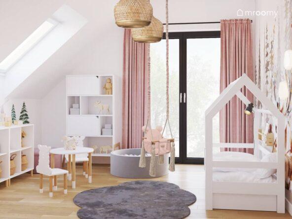 Jasny pokój dla małej dziewczynki a w nim łóżko domek wisząca huśtawka basen z kulkami stolik z krzesełkami z oparciami w kształcie alpak oraz szary dywanik w kształcie chmurki