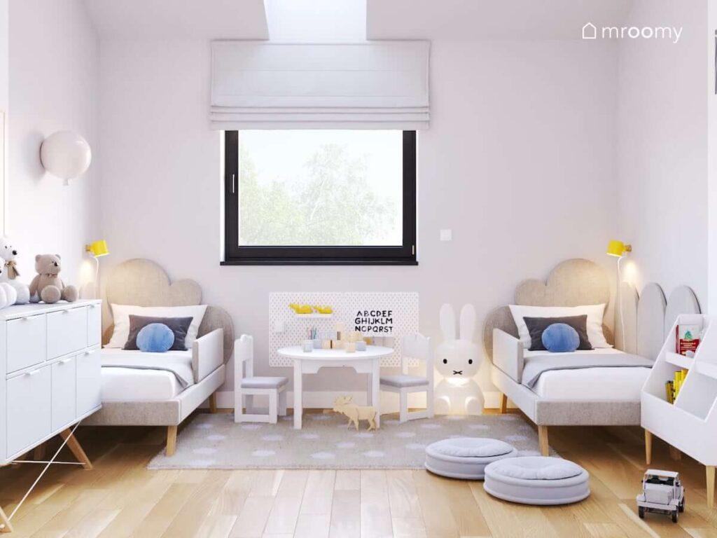 Jasny i przytulny pokoik dla rodzeństwa z szarymi łóżkami z zagłówkami w kształcie chmurek a także z białymi meblami