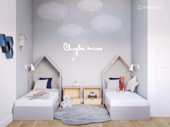 Strefa spania w pokoju dla rodzeństwa z łózkami w kształcie domków dywanem w kształcie chmurki oraz z ledonem w kształcie napisu i wiszącymi dekoracyjnymi chmurkami