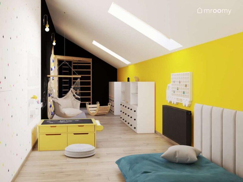 Biało żółto czarny pokój zabaw dla rodzeństwa z licznymi szafkami stolikiem kreatywnym oraz ścianką wspinaczkową i drabinką narożną