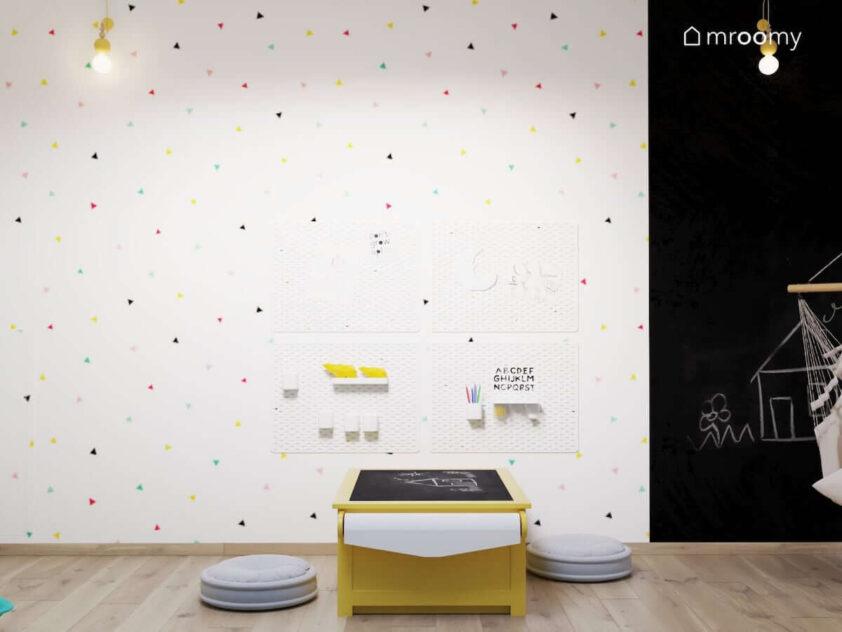 Ściana ozdobiona tapetą w kolorowe trójkąty a na niej organizery ścienne a na ziemi żółty stolik kreatywny i dwa siedziska w pokoju zabaw dla siostry i brata