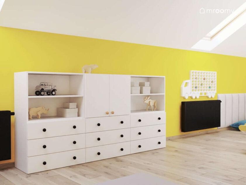 Biała szafka modułowa oraz półka na samochody w kształcie ciężarówki w biało żółtymi pokoju zabaw dla rodzeństwa