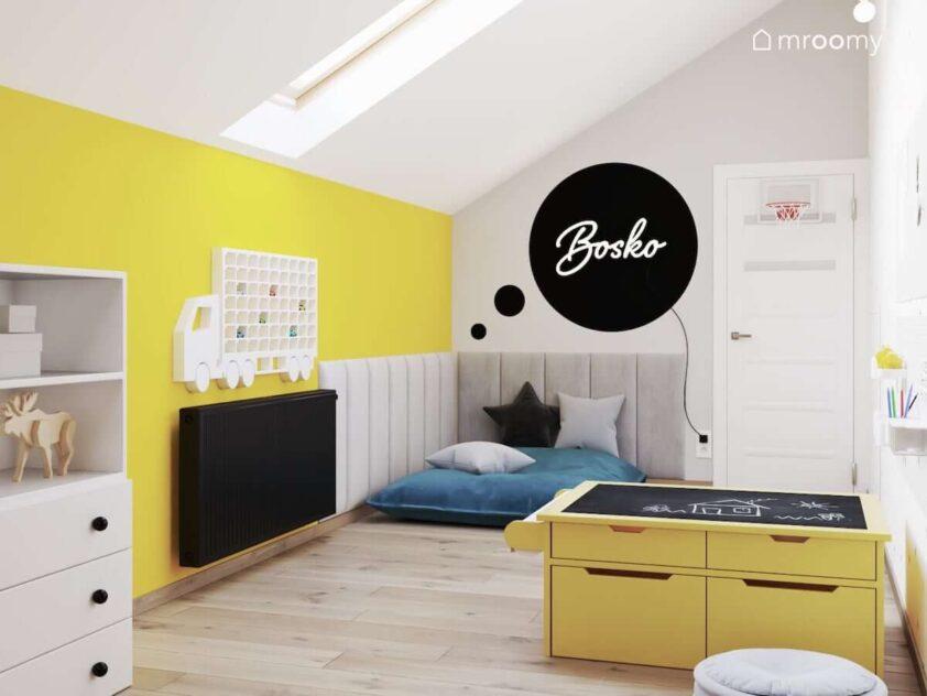 Biało żółty poddaszowy pokój zabaw dla rodzeństwa z wygodnym siedziskiem z poduszkami stolikiem kreatywnym a na ścianie miękkimi panelami ledonem w kształcie napisu i półką na samochody w kształcie ciężarówki