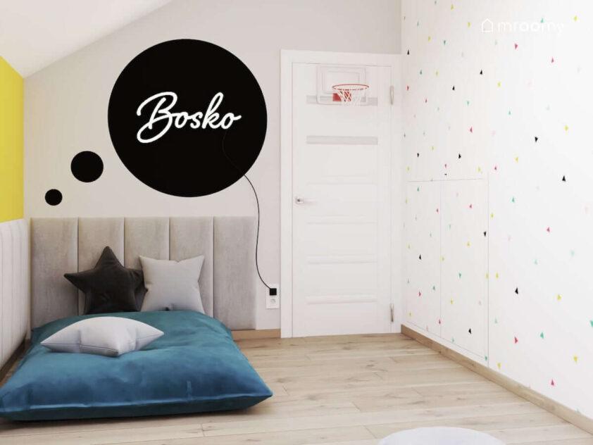 Duże miękkie siedzisko a na nim poduszki natomiast nad nim szare panele ścienne i biały ledon w kształcie napisu w jasnym pokoju dla brata i siostry