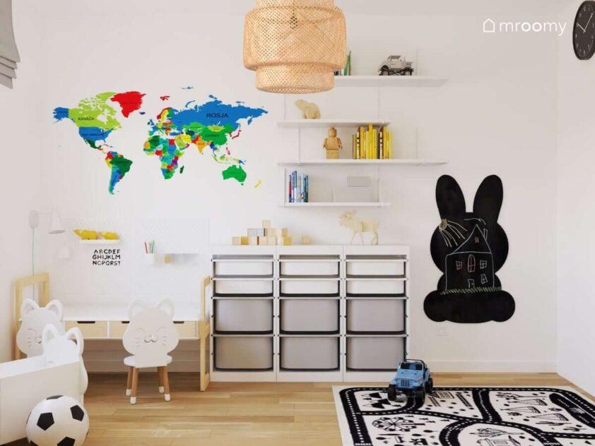 Jasny pokój dla rodzeństwa z regałem z pojemnikami na zabawki półkami ściennymi kolorową mapą świata tablicą kredową w kształcie królika oraz bambusową lampą
