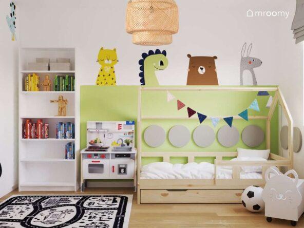 Drewniane łóżko w kształcie domku kuchenka dla dzieci oraz biały regał a na zielonej ścianie naklejki w kształcie zwierzątek w pokoju dla chłopca i dziewczynki