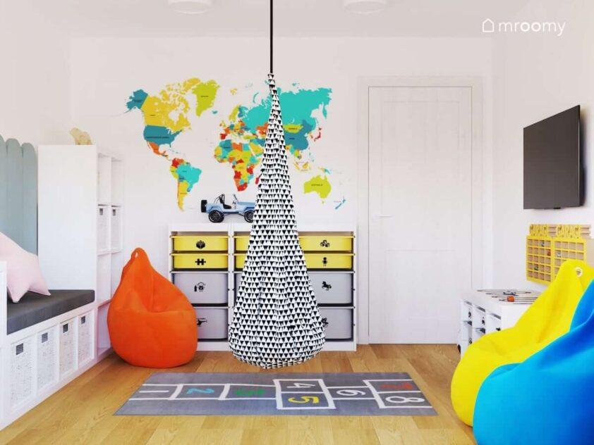 Jasny radosny pokój dla rodzeństwa z białymi ścianami i meblami oraz trzema pufami sako w różnych kolorach z kolorową mapą świata na ścianie i wiszącą huśtawką