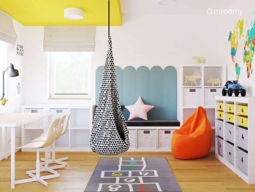 Biurko z trzema krzesłami siedzisko uzupełnione panelami ściennymi huśtawka kokon oraz pomarańczowa pufa sako w pokoju dla rodzeństwa