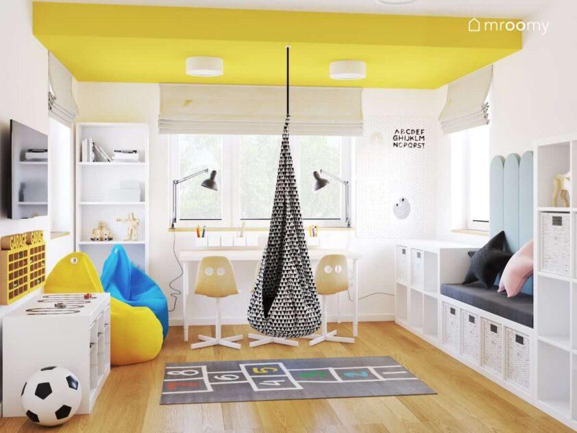 Biało żółty pokój dla trójki rodzeństwa z białymi meblami kolorowymi pufami sako i wiszącą huśtawką kokonem
