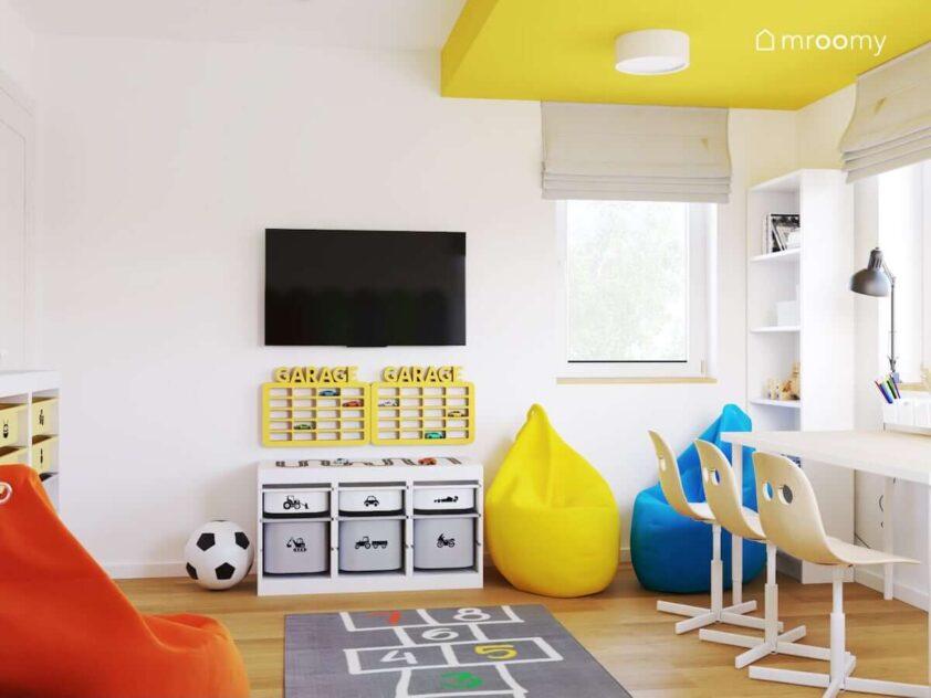 Regał z pojemnikami na zabawki żółte półki na samochody oraz telewizor i dywan we wzór gry w klasy w biało żółtym pokoju dla siostry i braci