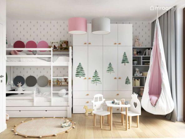 Jasny pokój dla rodzeństwa ozdobiony motywami choinek a w nim białe łóżko piętrowe uzupełnione panelami ściennymi a także duża biała szafa z gałkami w kształcie chmurek oraz różowa huśtawka kokon