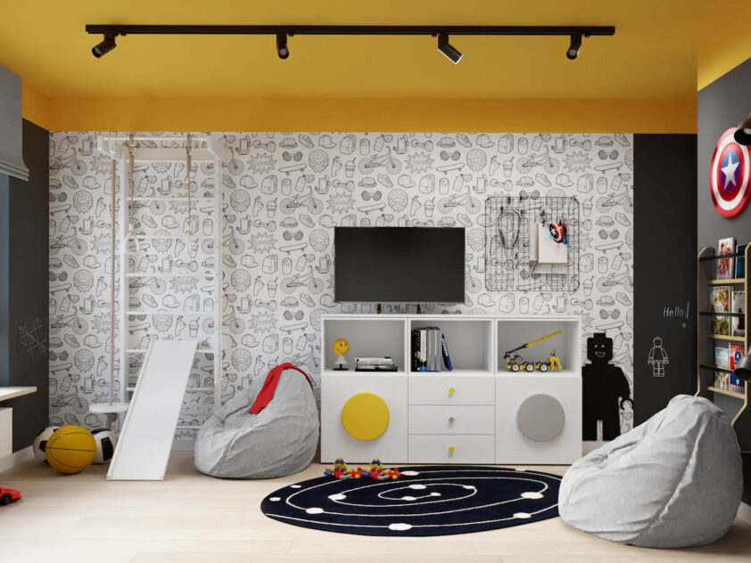 Ściana pokryta młodzieżową tapetą a na niej drabinka gimnastyczna ze zjeżdżalnią telewizor organizer i tablica kredowa w kształcie ludzika Lego w pokoju dla dwóch chłopców