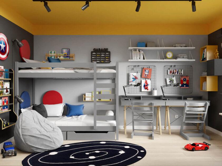 Szare łóżko piętrowe uzupełnione panelami ściennymi i drewnianymi półkami a także strefa nauki z dwoma biurkami organizerami ściennymi i półkami na książki w szaro czarno żółtym pokoju dla dwóch braci
