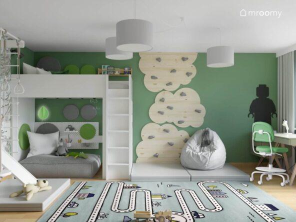 Białe łóżko na antresoli uzupełnione szarymi i zielonymi panelami ściennymi a pod nim przytulny kącik oświetlony przez lampkę w kształcie liścia a także ścianka wspinaczkowa w formie paneli w kształcie chmurek w pokoju dla kilkulatka
