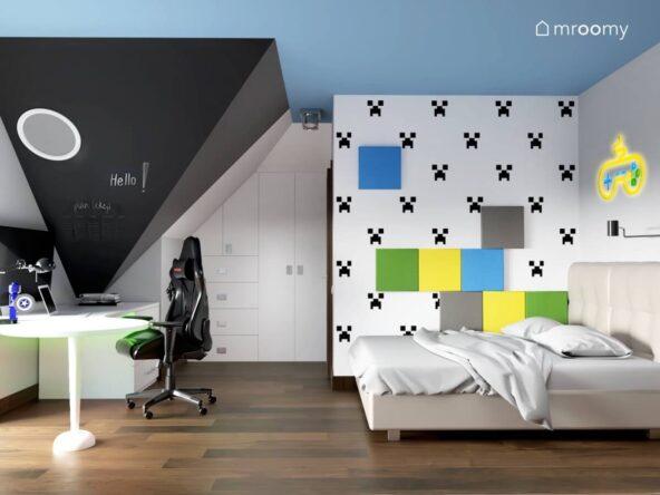 Poddaszowy pokój dla chłopca w wieku szkolnym a w nim ściana udekorowana tapetą z creeperem i panelami ściennymi w różnych kolorach a także biurko z fotelem gamingowym