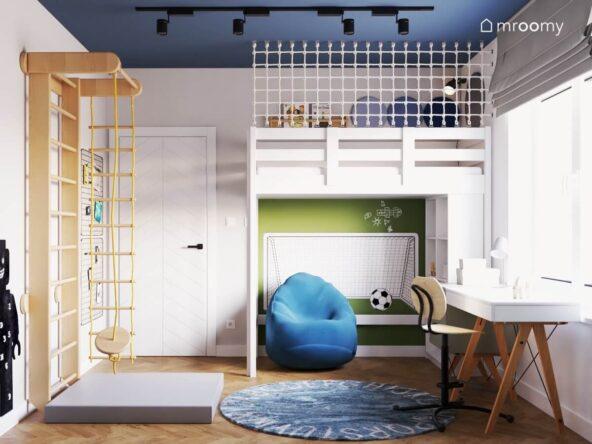 Białe łóżko na antresoli zabezpieczone siatką a pod spodem naklejka ścienna w kształcie bramki i niebieska pufa w szaro niebieskim pokoju dla chłopca