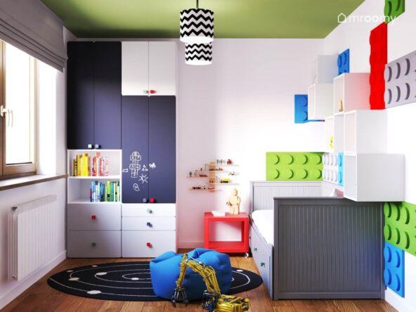 Biały pokój dla chłopca a w nim biało czarne meble z tablicowymi frontami oraz szare łóżko czerwony stolik nocny czarno biały dywan i niebieski worek do siedzenia