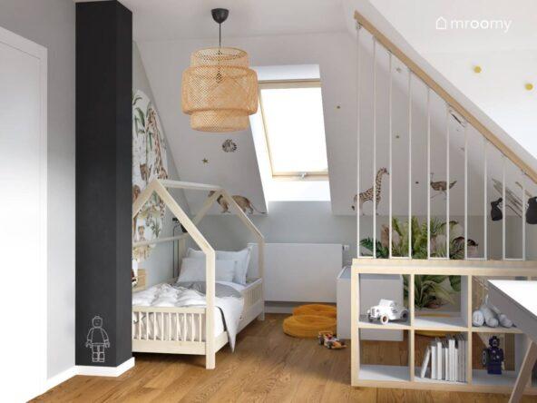 Drewniane łóżko domek biało drewniana krótka ścianka działowa oraz filar pomalowany czarną farbą tablicową a na suficie lampa bambusowa w jasnym poddaszowym pokoju dwóch chłopców