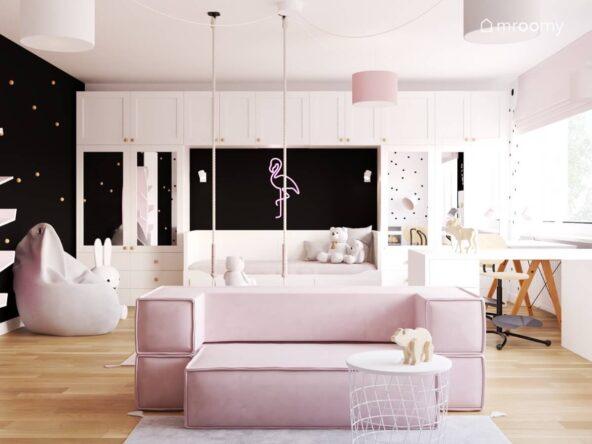 Białe meble modułowe różowa sofa pufa sako oraz ledon w kształcie flaminga na czarnej ścianie w pokoju dla dziewczynki