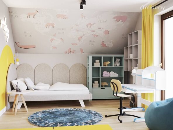 Kolorowy pokój dla dziewczynki z tapicerowanym łóżkiem miętowym regałem dywanem z alfabetem i tapetą w zwierzęta na skosie