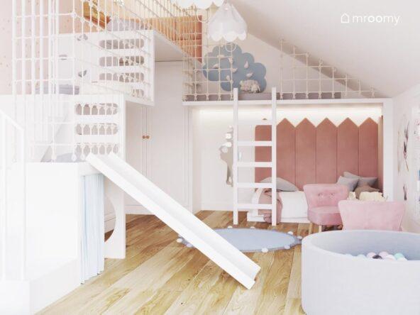 Wielopoziomowa antresola zabezpieczona siatką z demontowalną zjeżdżalnią a na niej ścianka wspinaczkowa w kształcie chmurki a pod spodem łóżko uzupełnione różowymi panelami ściennymi w kształcie sztachet