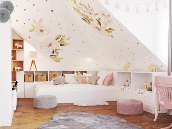 Biały pokój dla dziewczynki ze skosem ozdobionym naklejkami w kształcie magnolii i złotych gwiazdek a także białym łóżkiem i niską zabudową meblową