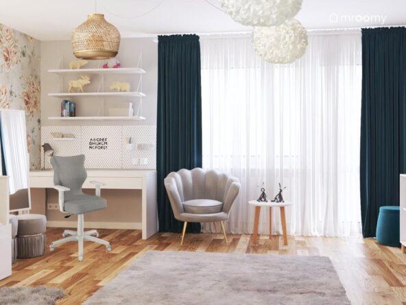 Szary pokój dla dziewczynki a w nim biurko z organizerami i półkami ściennymi szary fotel ze stolikiem na drewnianych nogach oraz lampy z bambusa i poliestru