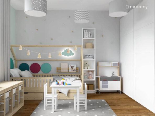 Drewniane łóżko domek uzupełnione girlandą z pomponów lampką nocną w kształcie chmurki i panelami ściennymi w różnych kolorach a także wąski biały regał i kuchenka dla dzieci w pokoju dla dziewczynki