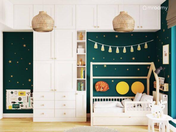 Białe meble modułowe z drewnianymi gałkami oraz drewniane łóżko domek uzupełnione miękkimi panelami i lampką nocną w kształcie sarenki a za nimi zielona ściana w gwiazdki w pokoju dla dwóch braci