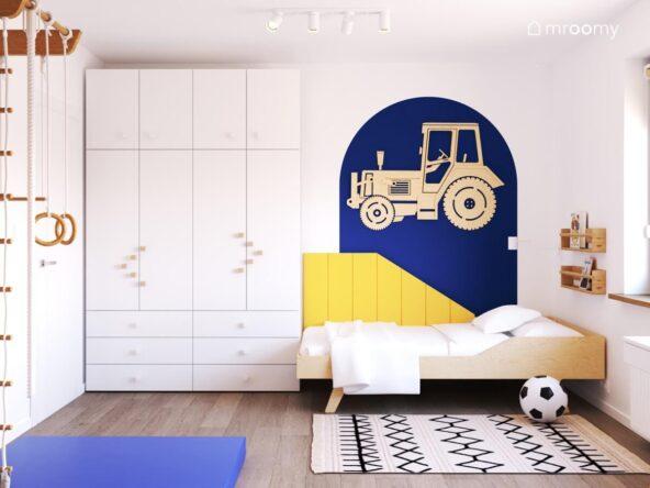 Biały pokój dla chłopca a w nim biała szafa drewniane łóżko a za nim żółte panele ścienne i traktor ze sklejki