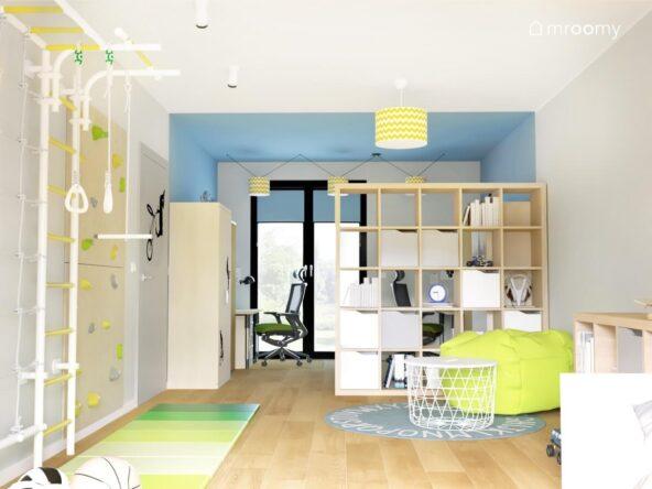 Biało niebieski pokój dla dwóch chłopców a w nim drewniany regał z wkładami drabinka gimnastyczna ścianka wspinaczkowa oraz zielone składane materace i zielony worek do siedzenia