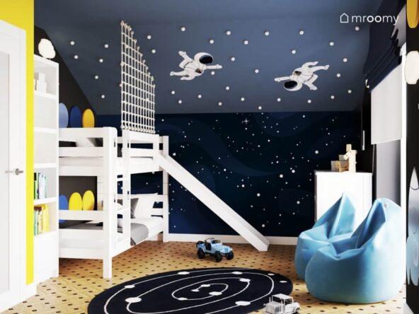 Kosmiczny pokój dla dwóch chłopców z białym łóżkiem piętrowym dwoma pufami dywanem z układem planetarnym oraz ze ścianą ozdobioną naklejkami w kształcie kosmonautów oraz gałkami imitującymi gwiazdy