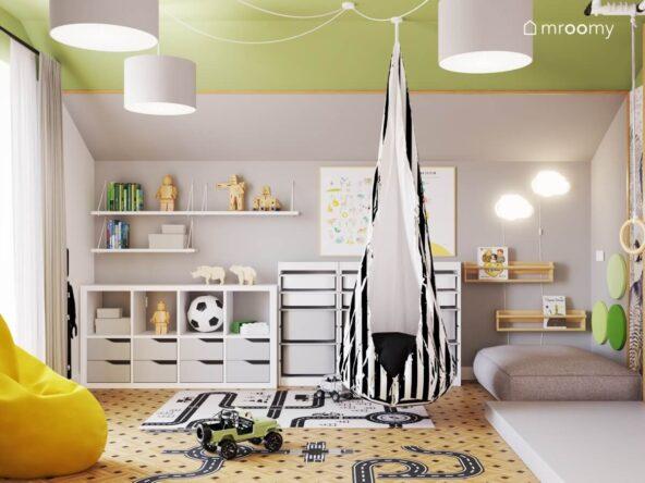 Szaro zielona bawialnia dwóch chłopców a w niej białe regały oraz półki ścienne ozdobne plakaty drewniane szafki na książki biało czarna huśtawka kokon oraz dywan z motywem miasta